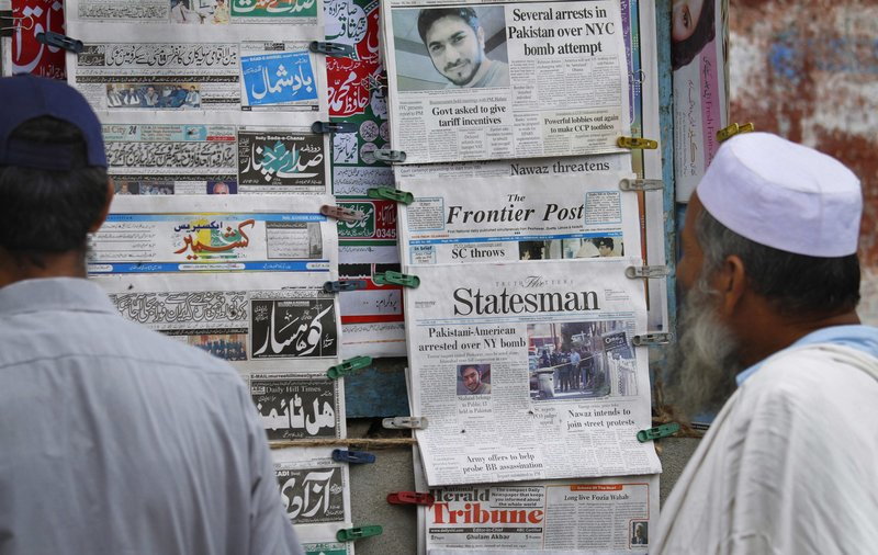 Pakistanis look at newspapers at a stall in Islamabad carrying headline stories on the arrest of a suspect in New York City's Times Square bomb attempt. Islamabad has received a formal request for an investigation from the U.S.