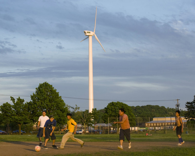 Soccer players take the field in Quinnipiac Park while a wind turbine spins on the grounds of Phoenix Press in New Haven, Conn., on Friday. In the drive for renewable energy, Connecticut is giving up on large-scale wind power, surrendering to poor topography and the limited reach of a shoreline that stops short of the Atlantic Ocean.