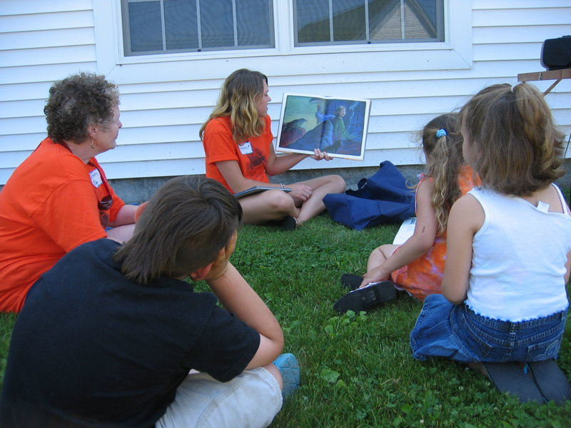Oxford Hills Bookmobile volunteer Chelsea Marshall reads a story to children as co-worker Betsey Foster, left, looks on. The mobile library will hit the road again beginning June 29.
