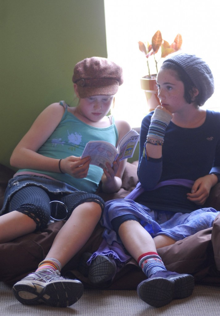 "Violet Sulka-Hewes, 10, and Madeline Curtis, 12, both students at the Friends School in Portland, listen to a reading at the Telling Room from ""Can I Call You Cheesecake?"""