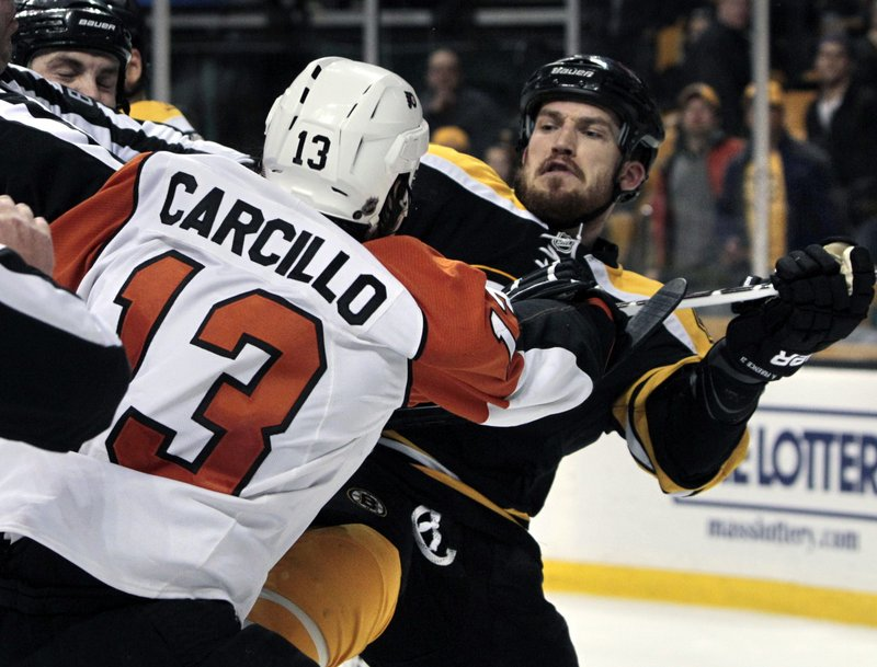 Flyers left wing Daniel Carcillo, left, mixes it up with Boston defenseman Andrew Ference as tempers flare and officials step in Monday night in Boston. The Flyers won, 4-0.