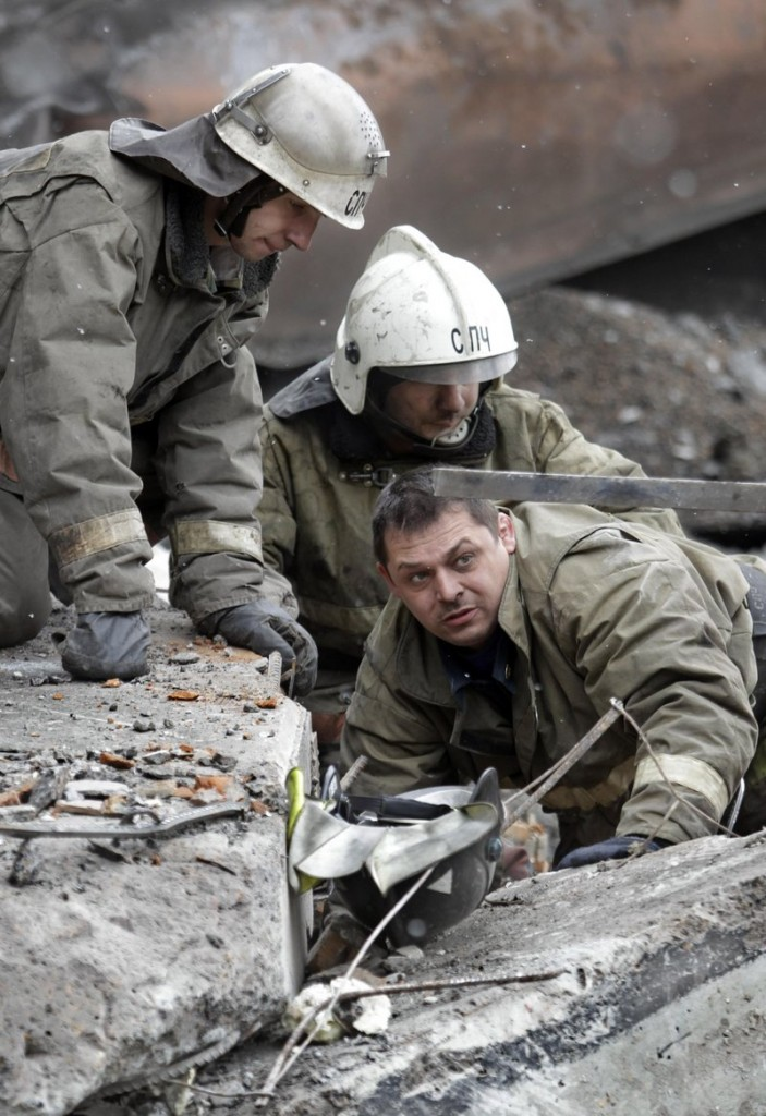 Emergency workers search the debris of the destroyed ventilation unit at the Raspadskaya mine in western Siberia on Tuesday. Two explosions tore through Russia's largest underground coal mine on Saturday, killing 52 people. Methane is being blamed for the explosions.