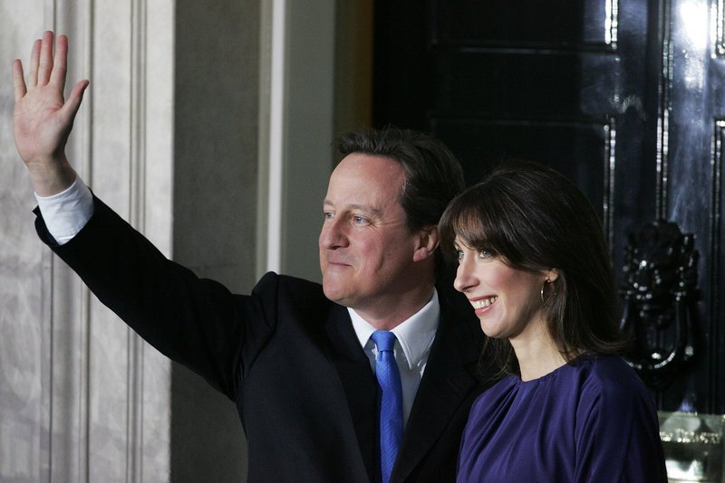 Prime Minister David Cameron and his wife, Samantha, greet the media Tuesday outside 10 Downing Street in London. The residence was vacated earlier by Gordon Brown.