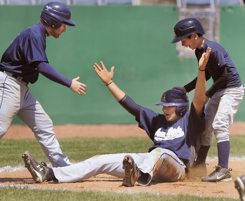 Mike Highland of Penn State Greater Allegheny raises his arms and accepts congratulations after scoring the winning run Tuesday against Southern Virginia in the USCAA tournament at The Ballpark in Old Orchard Beach.