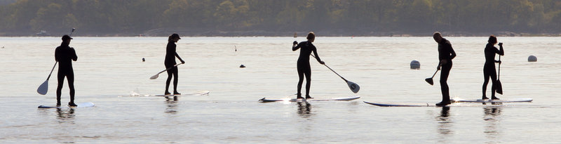 People travel by paddleboard across Casco Bay after attending a protest against offshore drilling on East End Beach in Portland on Wednesday.