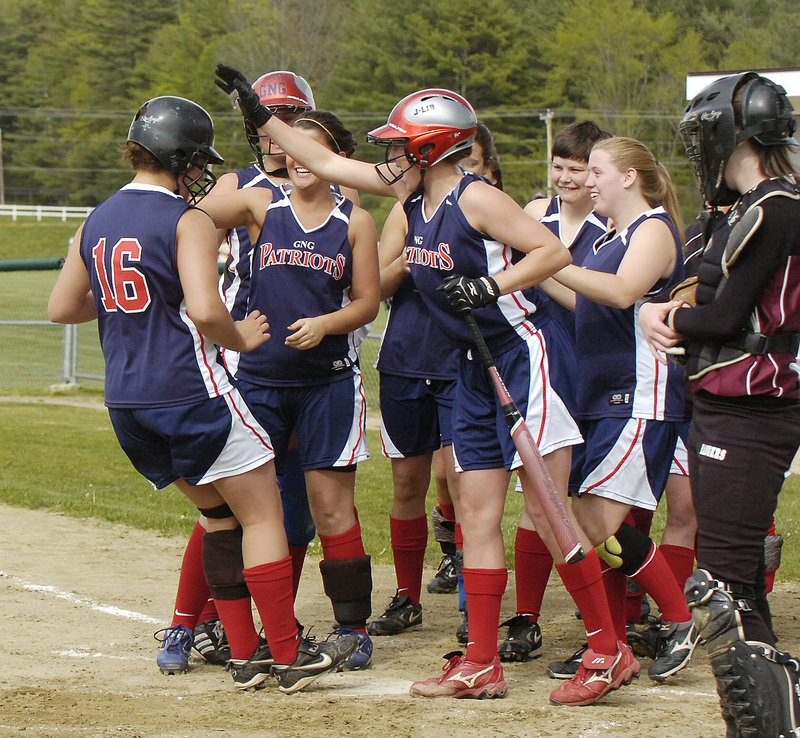 Abby Ryan of Gray-New Gloucester, left, gets the welcome home Wednesday after hitting a two-run homer in the first inning against Greely. Ryan later hit a second home run but it was Greely that emerged with a 9-7 victory.