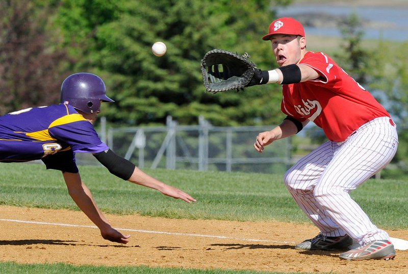 Louis DiStasio of Cheverus dives safely back to first, just ahead of the throw to South Portland's Zack Horton. The Riots won 4-3 Thursday. Both teams are now 6-2.