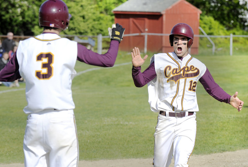 Rob Macdonald, who pitched a one-hitter for Cape Elizabeth, is met at the plate by Cam Brown after scoring in the third inning Friday. The Capers remained undefeated with a 5-1 victory at home against York.