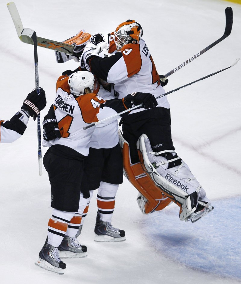 Philadelphia goalie Michael Leighton jumps into the arms of Mike Richards, center, and Kimmo Timonen after the Flyers completed their epic comeback Friday night with a 4-3 victory against the Boston Bruins.