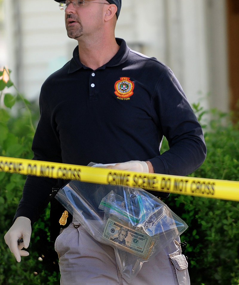 An FBI investigator carries a bag containing money as he departs a house at 39 Waverley Avenue in Watertown, Mass. The FBI raided the house early Thursday in connection with the failed car bomb attempt in New York City's Times Square.