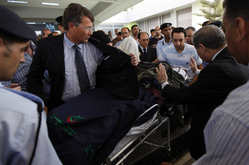 Police officers and medical officials shield 9-year-old Ruben van Assouw from the media as he leaves the hospital Saturday in Tripoli, Libya, for the flight home to the Netherlands. The boy, the sole survivor of Wednesday's Afriqiyah Airways crash, suffered two broken legs.