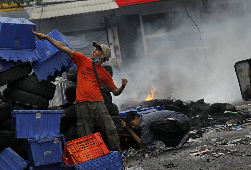 An anti-government protester fires a slingshot at Thai soldiers on Sunday in Bangkok, Thailand. About 30 civilians have been killed in the last four days, and about 59 since March.