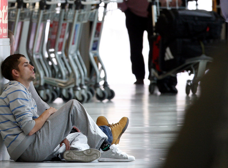 Travelers relax after flights were canceled at England's Newcastle International Airport on Sunday. The volcanic ash cloud has grounded 10 million travelers since April 15.