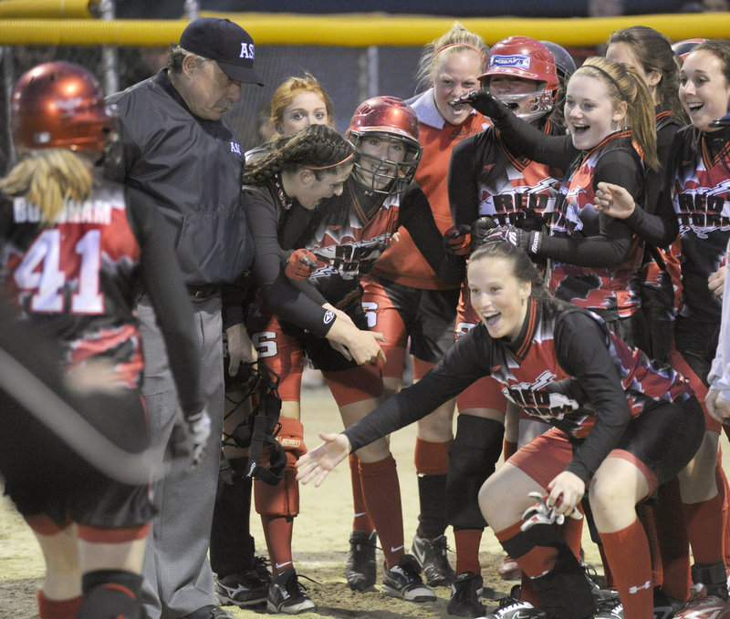 Scarborough players wait for Dominique Burnham to arrive at the plate after her grand slam.