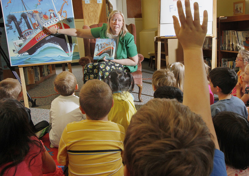 """First lady Karen Baldacci employs a visual aid as she reads """"Circus Ship,"""" written and illustrated by Chris Van Dusen of Camden, to students at Hall Elementary School in Portland on Tuesday."""