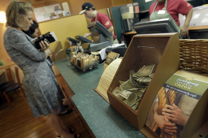 Customers order food as a cash box sits on the counter at Panera Bread in Clayton, Mo. The national bakery and restaurant chain's new nonprofit store allows customers to donate what they want for a meal.