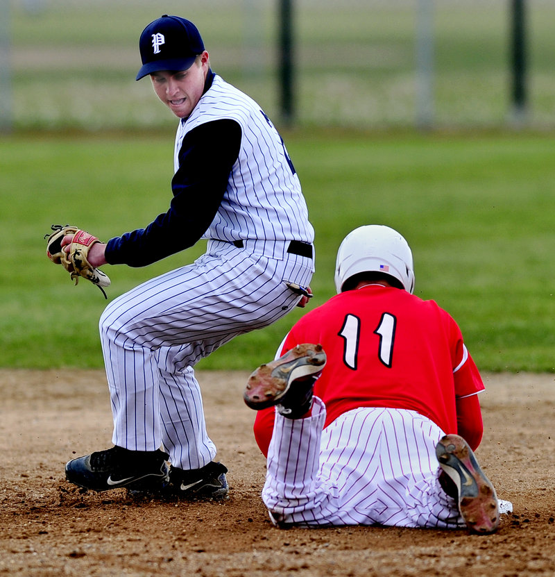 Ben DiBiase of Portland High snares a wide throw as South Portland's Evan Imdorf steals second with a headfirst slide in Tuesday's game at South Portland. The Red Riots posted a 2-0 victory.