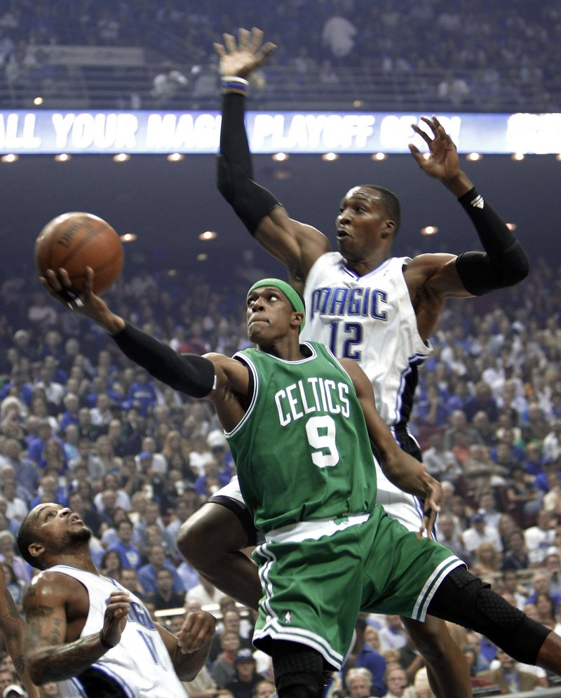 Rajon Rondo of the Celtics, left, does it again, scoring 25 points to help Boston slip by Dwight Howard and the Magic 95-92 on Tuesday night. Howard scored 30 points.