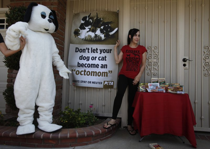 """Octuplets mom Nadya Suleman unveils a banner Wednesday in La Habra, Calif. """"I love animals and I do believe they should be spayed or neutered,"""" she said. """"Humans of course are much different."""""""