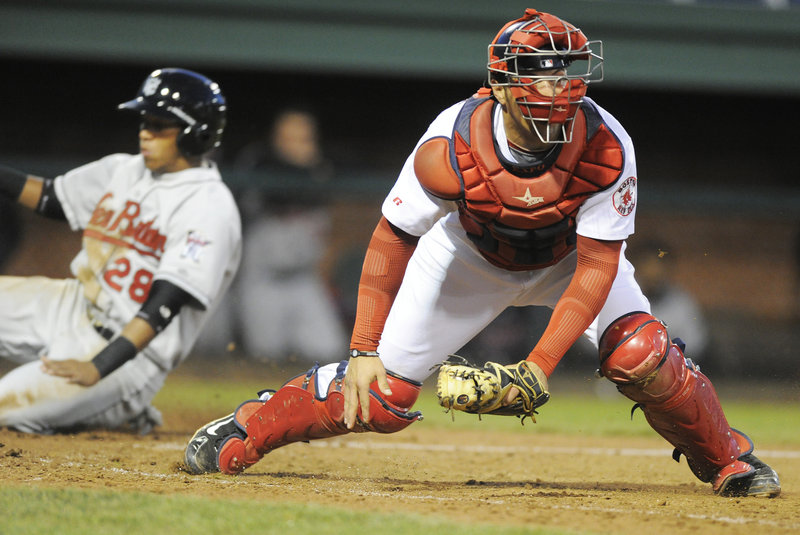 Portland catcher Luis Exposito looks for another play after an errant throw allows Yangervis Solarte, left, to score for New Britain. The Dogs lost 4-3 in 10 innings Wednesday.