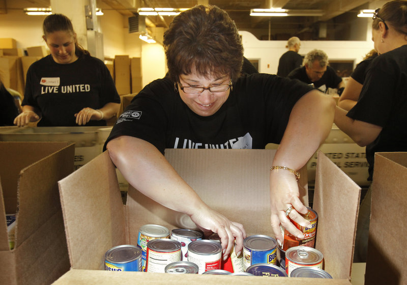 Gregory Rec/Staff Photographer Lisa Varela sorts canned goods while participating in the United Way Day of Caring in Portland on Thursday. The volunteers at this location sorted about 50,000 pounds of food gathered by The National Association of Letter Carriers – canned goods that the Salvation Army will in turn distribute to Portland-area food pantries.