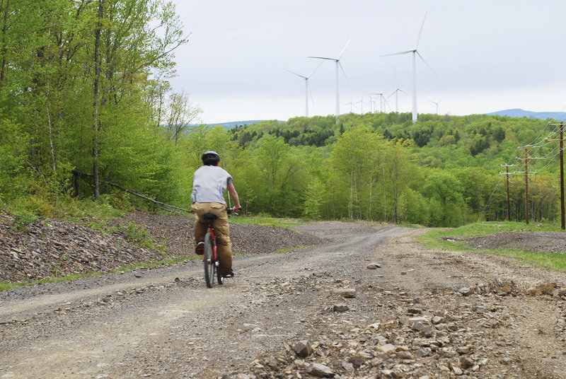 A competitor in the East Grand High School Adventure Race ascends Stetson Mountain amid wind turbines and stunning scenery. The high school outdoor education class hosted the May 8 race, which involved more than a mile of bushwhacking, nine miles of mountain biking,nine miles of canoeing and an optional climbing wall test.