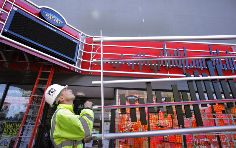 Josh Boyd of Burr Signs guides a section of the new marquee at Port City Music Hall in Portland on Friday. The city pitched in $18,000 of a federal grant as part of an effort to beautify the Congress Streets Arts District.