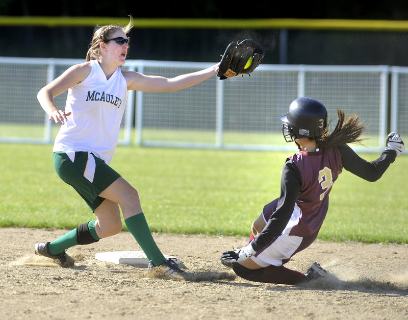 Sammi Martemucci of Thornton Academy slides safely into second base under a high throw as McAuley shortstop Sara Mercier tries to make the tag.