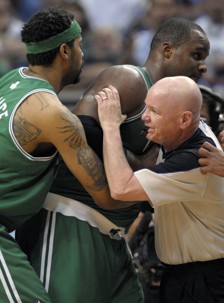 Rasheed Wallace, left, and referee Joe Crawford assist Glen Davis after he was hit in the face by an inadvertent elbow Wednesday night against Orlando, suffering a concussion.