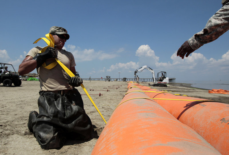 Louisiana National Guardsman Bryan Jones works Thursday on tidal dams that will protect shorelines from the oil spill at Grand Isle East State Park in Grand Isle, La.