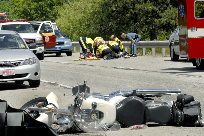Paramedics and state troopers attend to a motorcyclist who hit a guardrail on Interstate 95 in Augusta on Friday. Delmer Maxwell, 60, was flown by a LifeFlight helicopter to a Lewiston hospital with serious injuries.