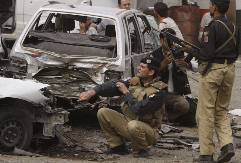 Pakistani police officers and others take cover near vehicles damaged in an attack outside the Garhi Shahu mosque in Lahore, Pakistan, on Friday. Militants attacked two mosques packed with hundreds of people from a minority Shiite sect.