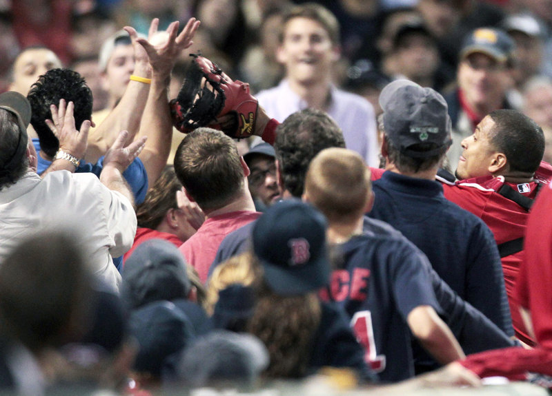A fan grabs a foul ball above the glove of Boston catcher Victor Martinez, right, in the fourth inning Friday night at Fenway Park. It was that kind of night for the Red Sox, who surrendered 20 hits and 12 runs to the Royals.