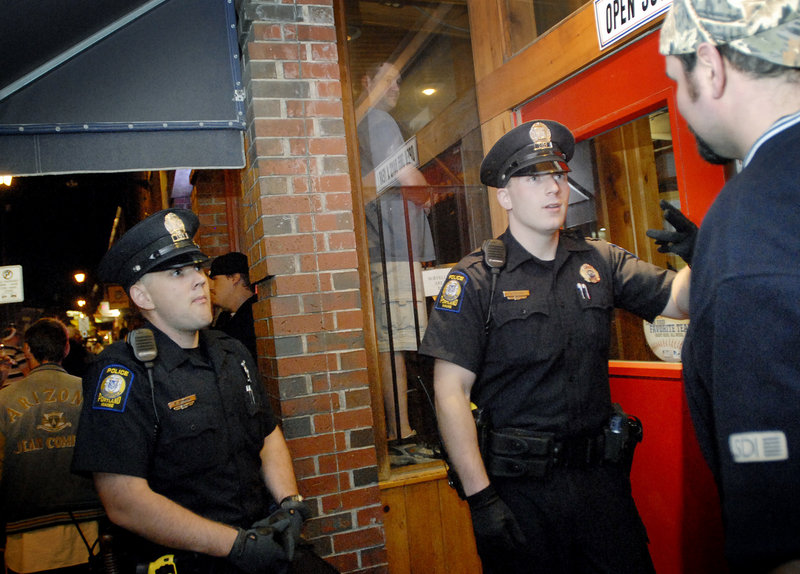Portland Police Officers Evan Bomba, left, and Vincent Rozzi confer with a doorman at a Fore Street establishment in the Old Port on Friday night.