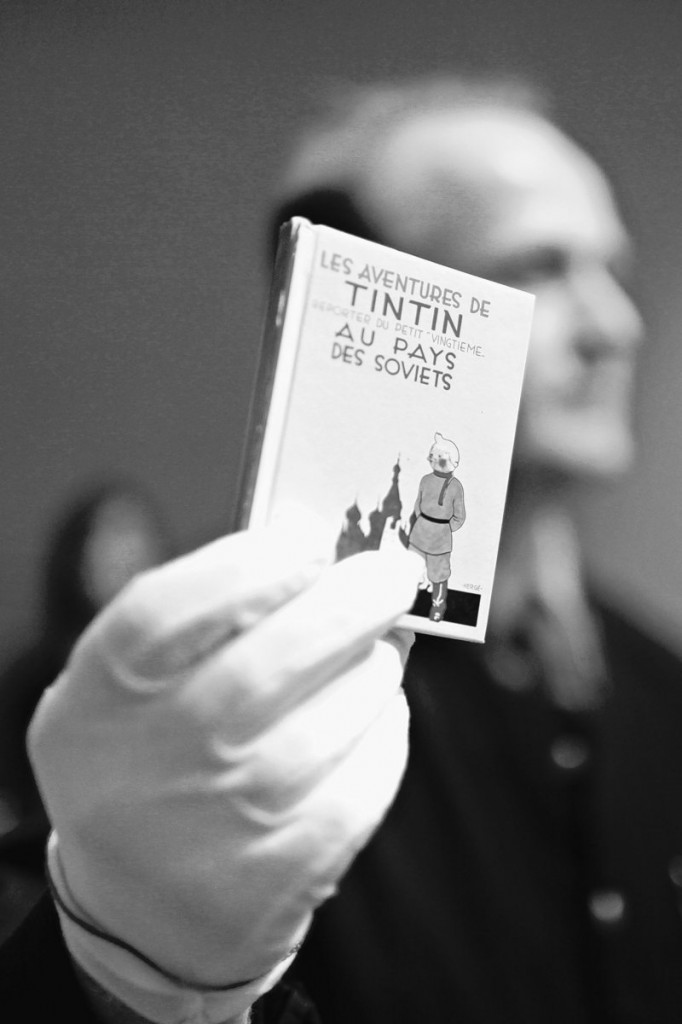 """A porter displays an album of """"Tintin au pays des soviets"""" drawn by Belgian creator Herge, during the auction of rare memorabilia of Tintin, at the Drouot-Montaigne auction house in Paris on Saturday."""