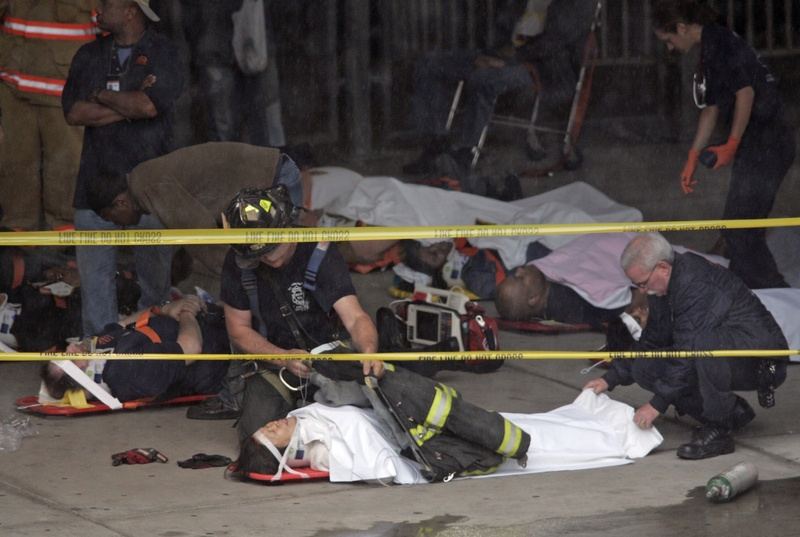 A member of the Fire Department of New York uses his coat to cover a person on a stretcher in a triage area set up in the St. George Ferry Terminal in the Staten Island borough of New York, today after a ferry boat struck a pier.