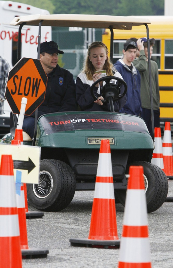 In this May 6, 2010 photo, Capt. Drew Bloom of the Vermont Department of Motor Vehicles, left, rides along with 10th-grader Hannah Chambers during a texting-while-driving event in White River Junction, Vt. While states pass laws banning texting while driving, some are going a step further, giving kids first-hand experience of the dangers of sending electronic messages while behind the wheel. They're sending kids through obstacle courses on golf carts while texting, keeping track of how many errors and fatalities they may cause.