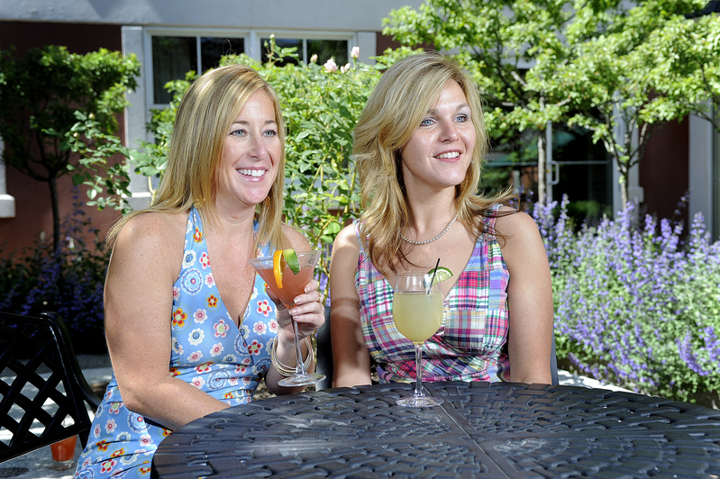 Outdoo decks and patios make for ideal places to enjoy summer-time cocktails and drinks. Tracy Demetteis (left) and Karen Gilbert enjoy a cocktail on the patio at Eve's in the Portland Harbor Hotel in Portland.