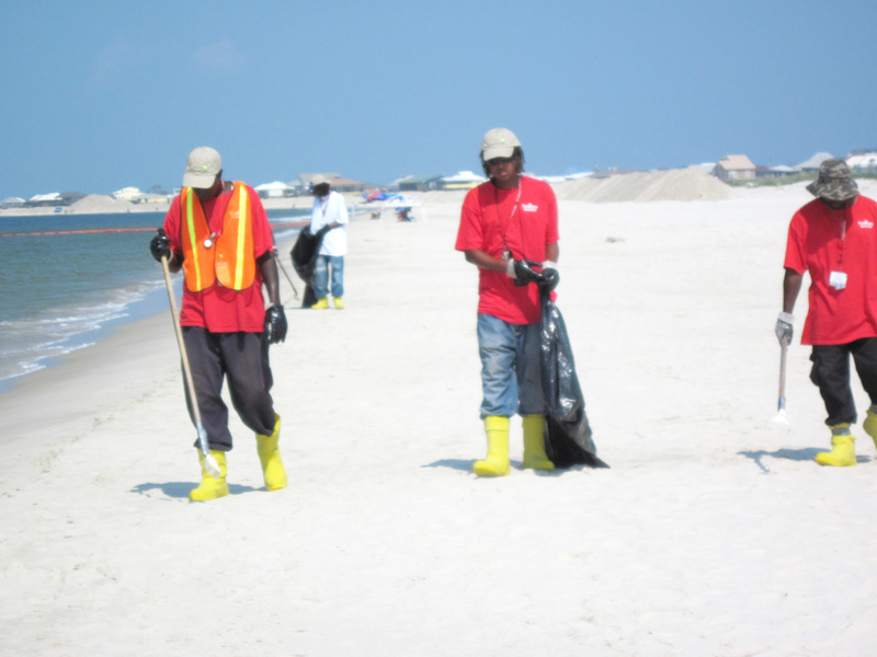 A cleanup crew patrols for oil Monday on a nearly deserted Dauphin Island beach. Out in the water, orange booms were positioned around the island to keep the oil from washing in.
