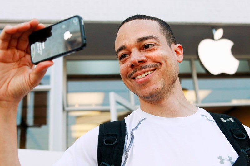 Thomas Smith, 32, of Boston, tries out the video on his new iPhone after standing in line outside the Apple Store in the Georgetown neighborhood of Washington, D.C., today.