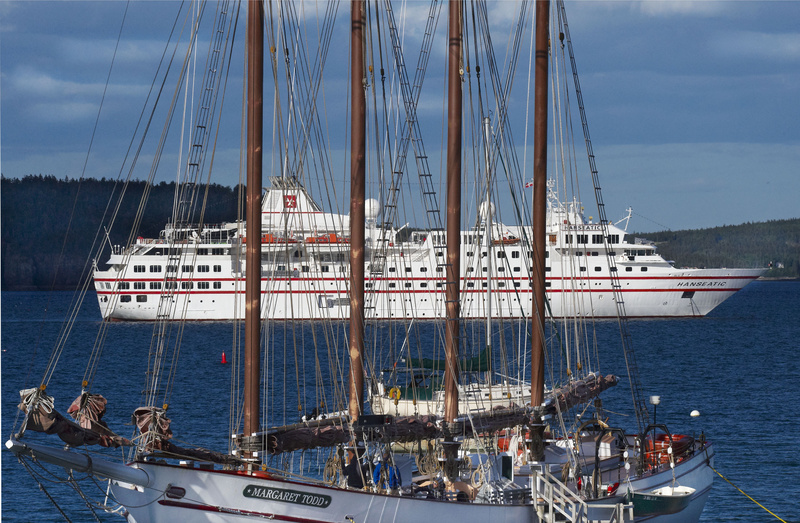 The four-masted schooner Margaret Todd sits at berth while the cruise ship Hanseatic sits at anchor in Bar Harbor on May 27. Bar Harbor expects 119 cruise ship visits this year, compared with only 39 visits 11 years ago.