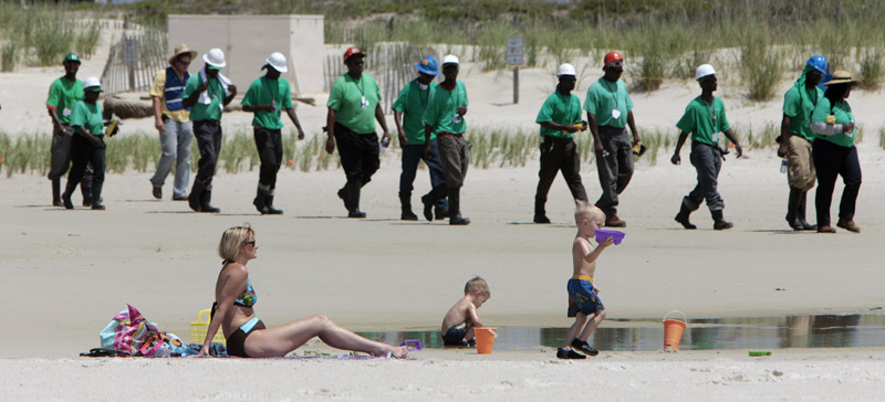Mary Smith of Theodore, Ala., watches over her grandchildren as a large crew of cleanup workers walk along the beach in Dauphin Island, Ala. Oil from the Deepwater Horizon disaster has started washing ashore on the Alabama coast.