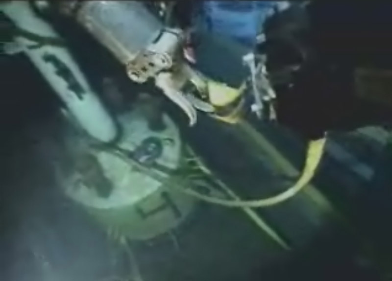 In this image from video made available by British Petroleum, a robot submarine prepares the capping device, lower left, early today.