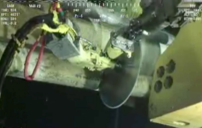 In image made from video released by British Petroleum, robot submarines use a circular saw-like device to cut a pipe at the Deepwater Horizon oil rig.