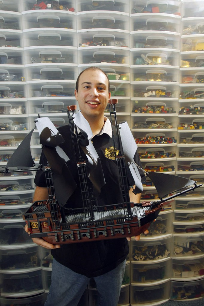 Piccirillo shows off a pirate ship he built from scratch. In the background are dozens of container drawers filled with thousands of Lego pieces that allow Piccirillo uses to build custom projects.