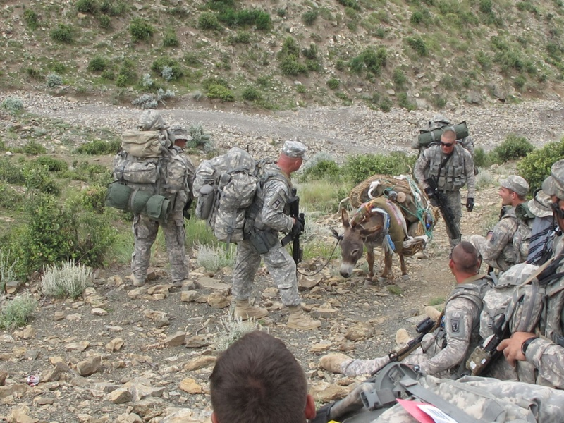 Soldiers from Bravo Company's Second Platoon watch as Sgt. Johnathan Weeks of Ellsworth and Spc. Jeffrey Holmes of Houlton coax a pack donkey up the mountain trail to their observation post high atop a mountain in eastern Afghanistan.