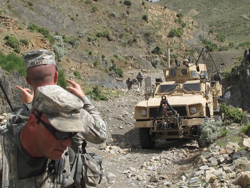 """Staff Sgt. Joshua Holmes of Lisbon Falls guides a Bravo Company vehicle up a """"wadi,"""" or dry riverbed, in a remote valley of eastern Afghanistan. In the foreground is Sgt. Frederick Moody of Gorham."""