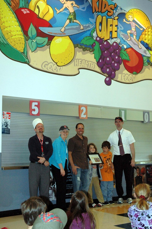 Wells-Ogunquit Community District Food Service Director Tyler Goodwin, Wells Elementary School Principal Marianne Horne, Wells resident Jason Talevi, Talevi's daughter Olivia and son Jack and Assistant Superintendent Ken Spinney pose in front of a mural Talevi created and donated to the school in support of its nutrition promotion campaign.