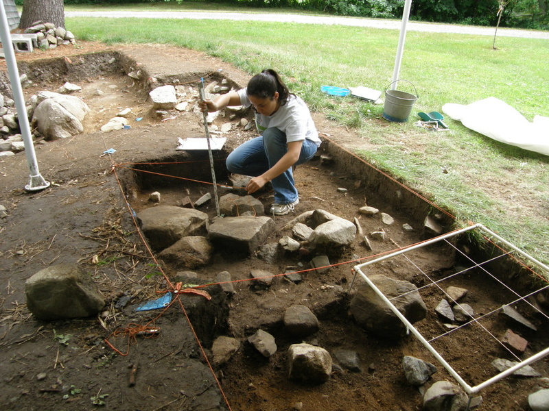 A student at the Damariscotta River Association's Archaeology Field School measures soil depth in an excavation grid at the Bryant-Barker Tavern Site in Newcastle.