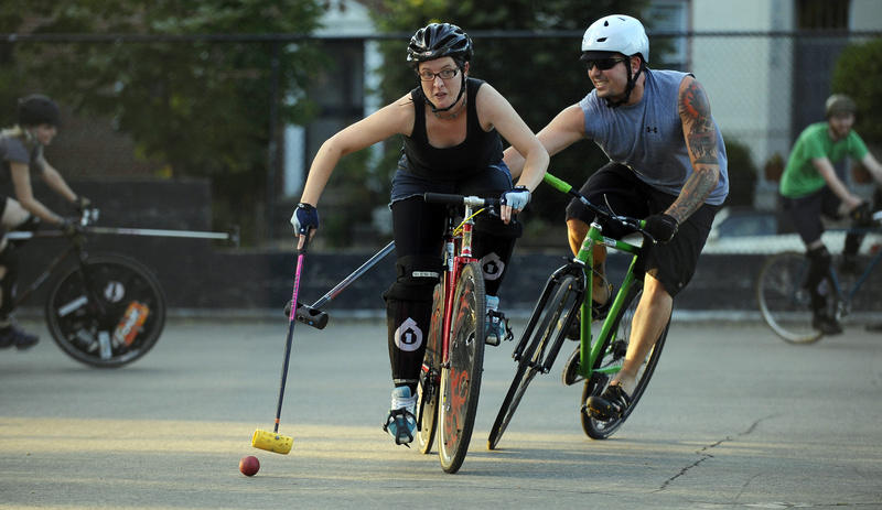 Shane Murphy chases Jess Horning in a hardcourt bike polo match.